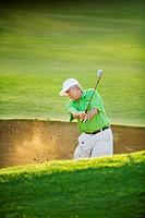 Hawaii, Maui, Male golfer swinging golf club at the Maui Country Club course.