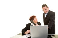 Man wearing a suit shouting at a woman sitting at a desk in front of a laptop