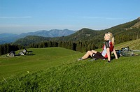 Blonde woman with a mountainbike sitting on a meadow, view of the Ebenforstalm Alpine Pasture, Kalkalpen National Park, Upper Austria, Europe