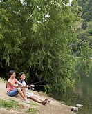 Young boy and girl fishing in lake