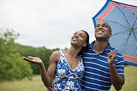 African couple with umbrella checking for rain