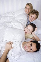 Family lying in bed together, smiling at camera