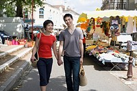 Asian couple waking at outdoor market
