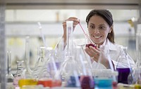 Mixed race scientist working in laboratory with beakers of liquid