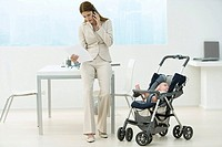 Professional woman in office with baby in stroller, talking on cell phone