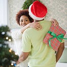 Mixed race woman hugging boyfriend and holding Christmas present