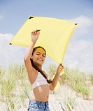 Hispanic girl flying kite on beach