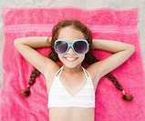Hispanic girl laying on beach in bikini and sunglasses