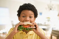 Mixed race boy eating healthy sandwich