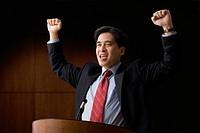 Cheering Chinese businessman speaking at podium