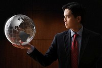 Chinese businessman holding glass globe