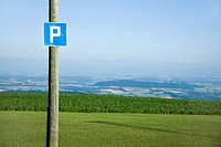 Road sign of the letter p, countryside in background