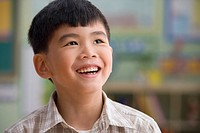 Asian boy smiling in classroom