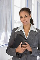 African businesswoman holding binder