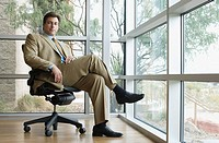 Confident Hispanic businessman sitting in chair