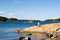 Man sitting on a rock, Finnhamn Island, skerry, Stockholm archipelago, Sweden