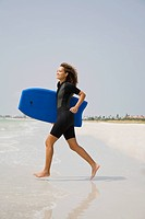 Mixed race woman running with boogie board at beach