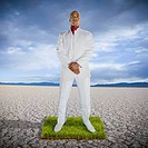 African man standing on patch of grass in desert