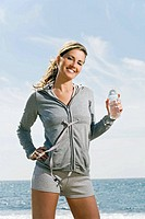 healthy woman with a bottle of water by the sea