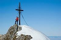22_year_old woman, summit cross on Mt Steinernen Jaeger, pre_Alps near Reichraming in the winter, Upper Austria, Austria, Europe