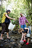 Family picking up litter in creek