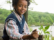 A boy doing an experiment on a plant