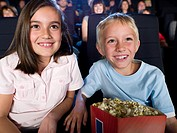 A boy and girl watching a movie
