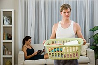 A man doing laundry whilst a woman relaxes (thumbnail)