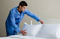 A man tidying the bed