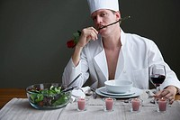 A man in a chefs outfit with a rose in his mouth