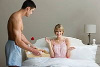 A man surprising a woman with breakfast in bed