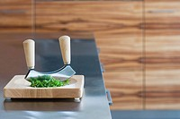 Herb cutter and herbs on a chopping board