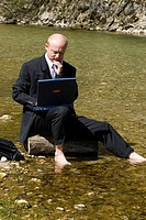 Businessman working while sitting in a mountain brook