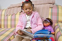 A child reads to her doll