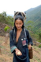 Sowing mountain rice, ethnic Akha woman, dressed in traditional costume, holding rice grains in her hand, Phongsali province, Laos, Asia