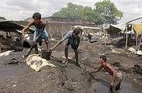 Many slum dwellers live off recycling industrial waste. Day labourers wash industrial slag in search of residual metal. Young men dispose of already w...