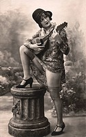 Woman playing plucking instrument, leaning against a pillar, historic picture from about 1920