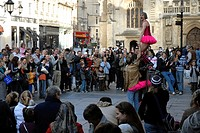 Street performer, busker riding a unicycle in front of a large crowd, Bath, Somerset, England, UK