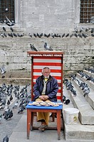 Vendor selling pigeon feed in front of a mosque in Istanbul, Turkey