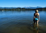 Woman wading into a lake, pre_Alps, Bavaria, Germany
