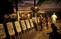 Artwork for sale being admired by tourists on the beach promenade at dusk, Puerto Vallarta, Jalisco, Mexico