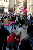 Crowd of onlookers watching a street performer on a unicycle, Bath, England, UK