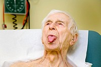 Tongue examination. 93 year old male patient sticking out his tongue during a check_up at the hospital. He has previously suffered a transient ischaem...
