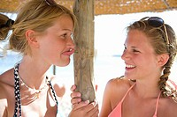 Teenage girls making faces under beach umbrella