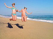 Teenage girls jumping on beach