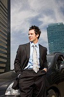 Businessman standing in front of car