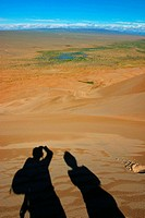 Shadows of two hikers on the top of Khongoryn Els sand dunes in the evening light, Gobi Gurvansaikhan National Park, Mongolia