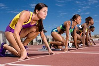 Female runners at starting block kneeling on race track