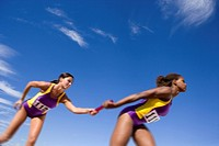 Female athletes passing relay race baton