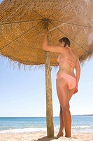 Teenage girl standing under beach umbrella (thumbnail)